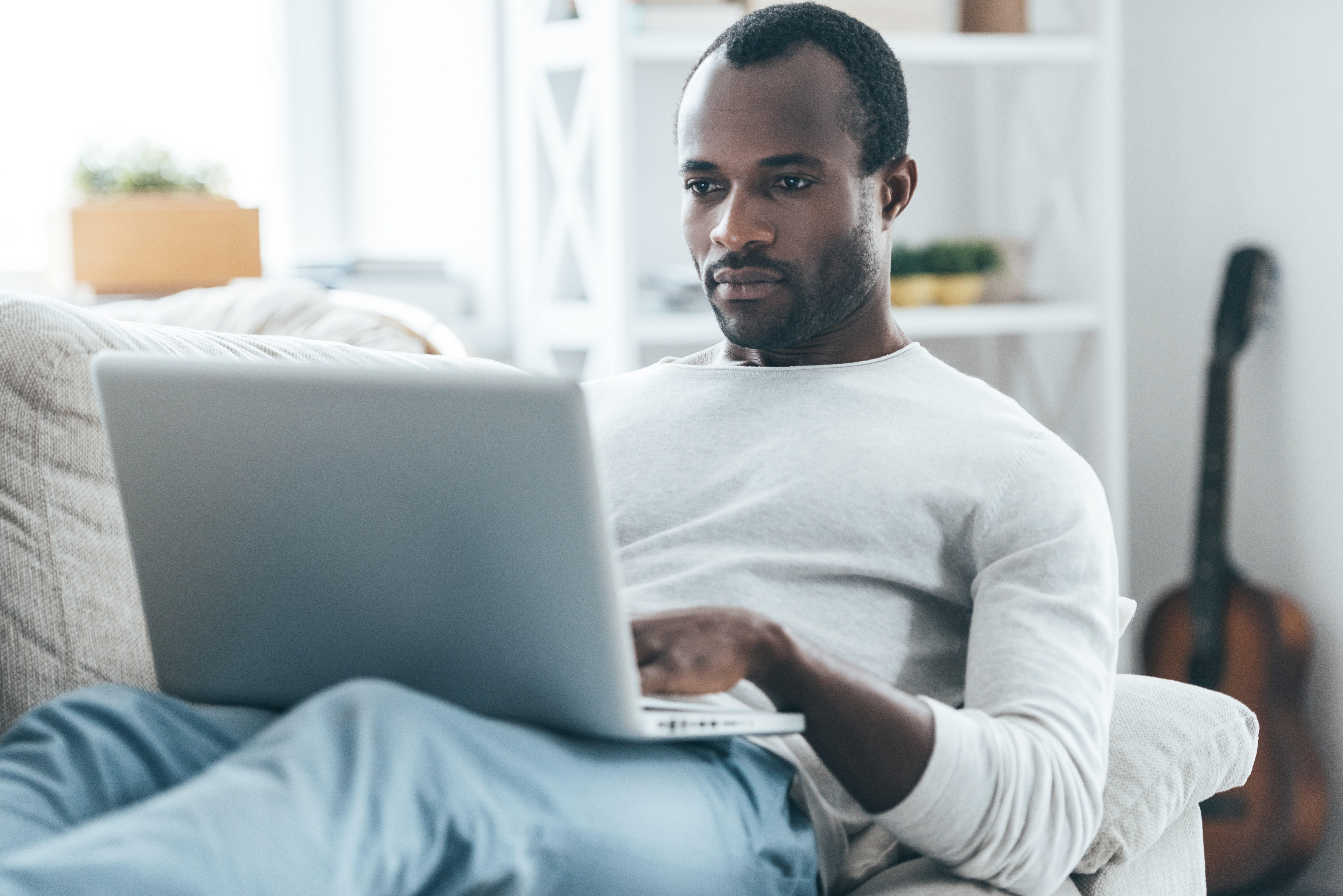man lounging on sofa looking at laptop